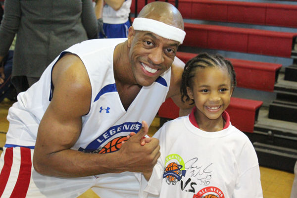 Jerome Williams and young basketball player posing and smiling for pictures.