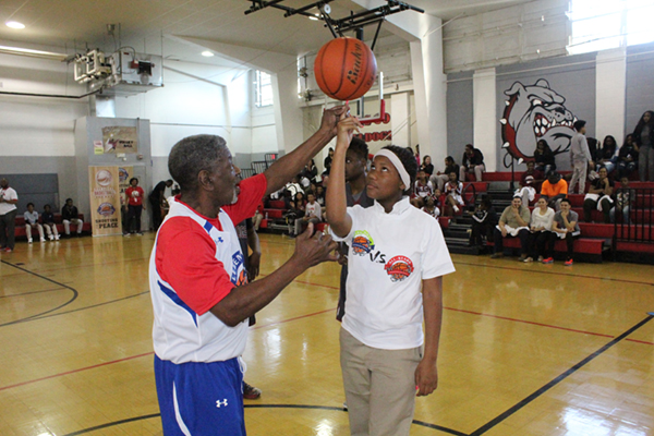 Young basketball player spinning a ball on his finger.